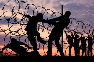 Concept of security. Silhouette of refugees climb over the barbed wire at the border